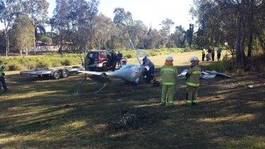 Investigators at the scene of a light plane crash in Runcorn, south of Brisbane.