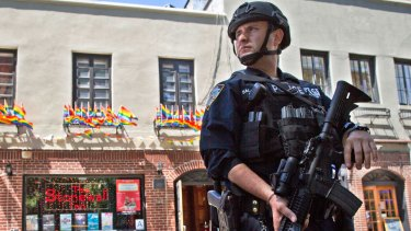 An armed police officer stands guard outside a pub in New York after a gunman attacked at a gay nightclub in Orlando, Florida.