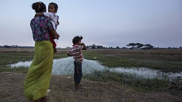 A family looks out over the mostly dry rice paddy fields near their home in Dala, Burma, on Sunday.