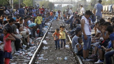 Children play on a train track as migrants wait for a train heading toward Serbia, at the railway station in the southern Macedonian town of Gevgelija in August 2015.