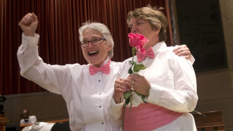 Barbra Schwartz, left, Julia Troxler celebrate after being married in a mass wedding at the Fulton County Government Centre on Friday in Atlanta.