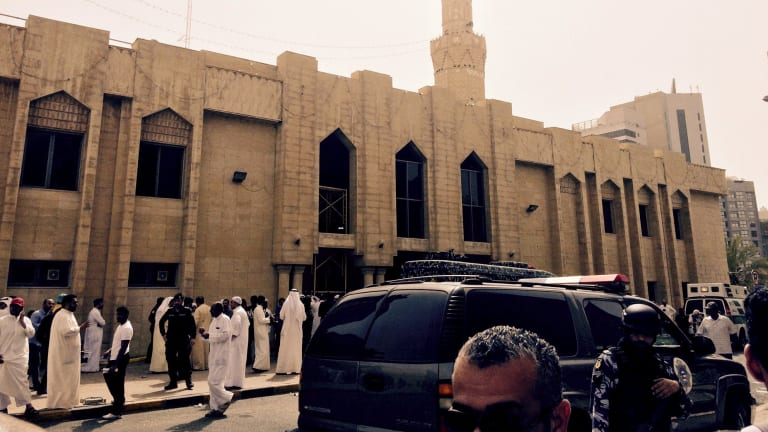 Police control the crowd in front of the Imam Sadiq Mosque after a bomb explosion, in the Al Sawaber area of Kuwait.