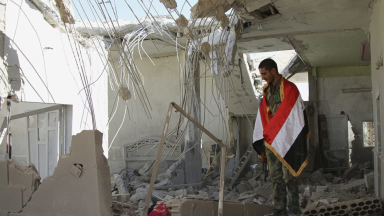 A Syrian soldier wrapped in a Syrian flag stands in a damaged house in Achan, Hama province, Syria, on Sunday.