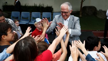 Prime Minister Malcolm Turnbull gives high-fives to children during his visit to the Australian International School in Hong Kong