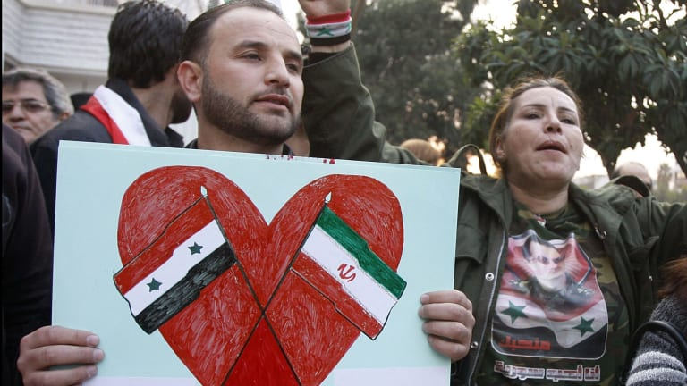 A pro-Syrian regime protester holds a placard showing the Iranian and Syrian flags to thank Iran for its support of the Syrian regime, in Damascus in November.