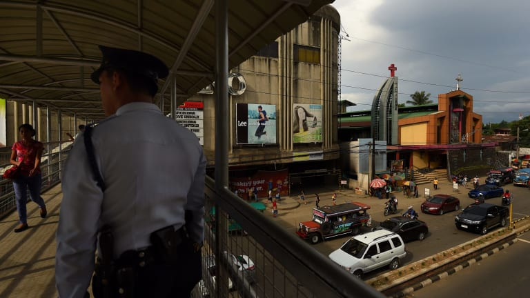 A police officer stands on the overpass connecting two malls in Cagayan De Oro where two of Peter Scully's victims were allegedly groomed by his girlfriend.