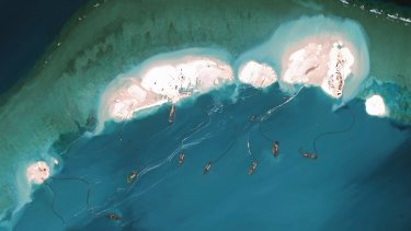 A handout satellite image shows dredgers working at the northernmost reclamation site of Mischief Reef, part of the Spratly Islands, in the South China Sea in March 2015.