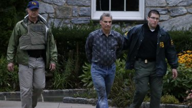 Pastor Vitaly Korchevsky is escorted in handcuffs from his home by agents from the Federal Bureau of Investigation in Glen Mills, Pennsylvania, on August 11.