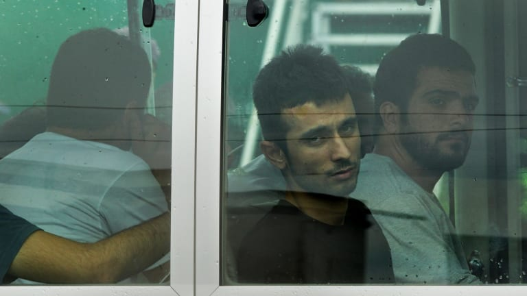 Asylum seekers look out the window of the bus after arriving on Manus Island.