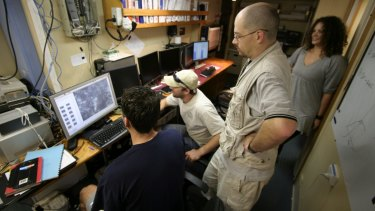 The research team study the first underwater images from their mission off Ribbon Reef .
