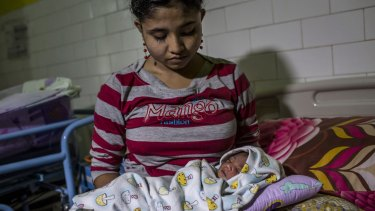 Rohingya refugee Samsidar, 15, holds her two-day-old baby at a hospital in Bayeun, Aceh. Persecution of the Muslim minority has escalated in recent years.