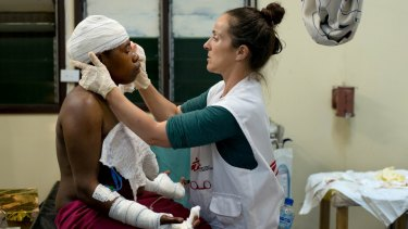 Irish nurse Aoife Ni Mhurchu treats a patient last year at Tari Hospital in the highlands region of Papua New Guinea. The woman sought treatment for lacerations after her husband cut her with a knife on the back of her head and both hands.