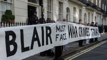 Protesters hold up a banner reading 'Blair must face war crimes trial' outside the London home of former British prime minister Tony Blair on July 6.