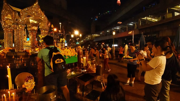 People pray at Erawan Shrine in Bangkok on Thursday following the death of the King.
