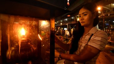 A young woman lights a candle before praying at Erawan Shrine in Bangkok on Thursday.
