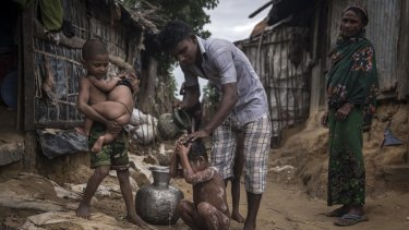 A refugee bathes his child at the Kutupalong  Camp in Teknaaf, Bangladesh.