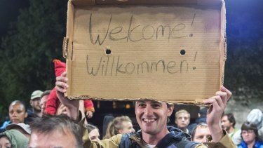 Crowds welcome refugees at the train station in Saalfeld, central Germany. Hundreds of refugees arrived by train from Munich to be transported by buses to an accomodation centre.