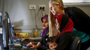 Zoe Seeberg-Gordon (centre) from the Australian Multicultural Foundation teaching IT skills to recent migrants so they can better understand what kids are looking at online.