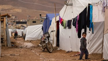 A young Syrian refugee walks past tents at the al-Nihaya camp in the eastern Lebanese town of Arsal, where some reports say Saja Hamid al-Dulaimi and her son were arrested.