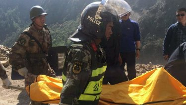 Rescuers carry the body of a woman in Gyirong county,Tibet. She was killed by falling rocks after a 7.3-magnitude earthquake hit the Tibet-Nepal border on Tuesday.