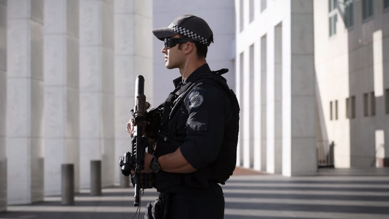An AFP officer armed with an SR-16 stands guard to the front of Parliament House.
