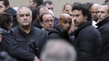 French President Francois Hollande, centre, flanked by security forces arrives at the office of satirical magazine <i>Charlie Hebdo</i> in Paris.