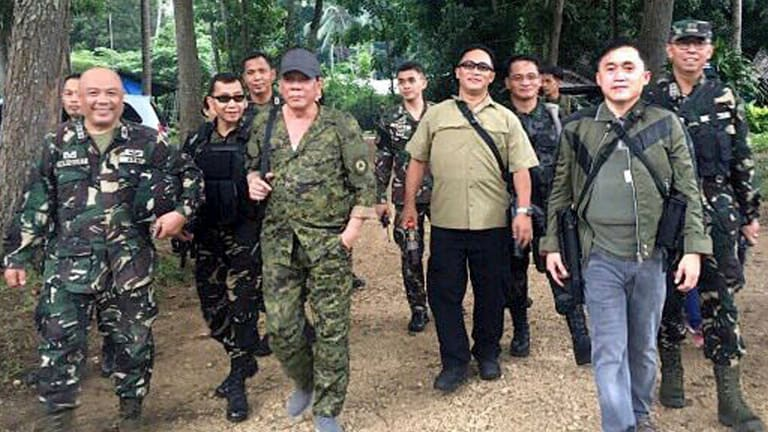President Rodrigo Duterte, centre left, wearing a bullcap and an assault rifle slung on his shoulder, walks with  military officers   on the outskirts of Iligan city in the southern Philippines on Friday. Mr Duterte was supposed to fly to Marawi city but was forced to cancel  due to inclement weather.