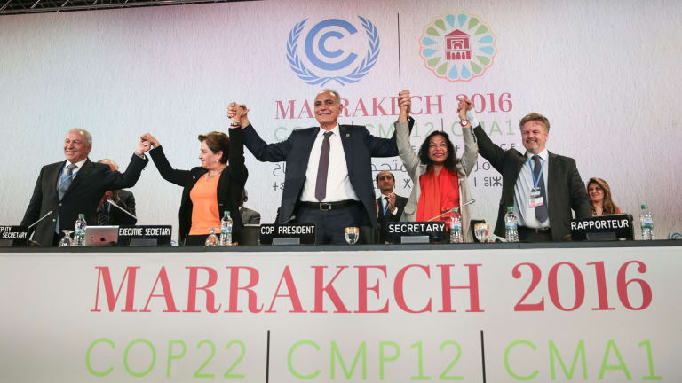 UN climate chief Patricia Espinosa, second left, and Morocco's Foreign Minister Salaheddine Mezouar, centre, celebrate at the COP22 climate change conference in Marrakech.
