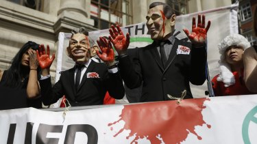 Bloddy hands: Protesters wearing Tony Blair and George W. Bush masks pose in London, shortly before the publication of the Chilcot report.