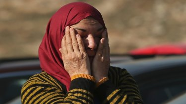 A Syrian woman evacuated from Aleppo waits to cross into Turkey.
