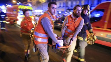 A woman is evacuated from the Bataclan theatre in Paris on Friday night.
