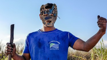 A masked gatekeeper guards a blocked road to Yvu Farm in the aftermath of Santos' death.