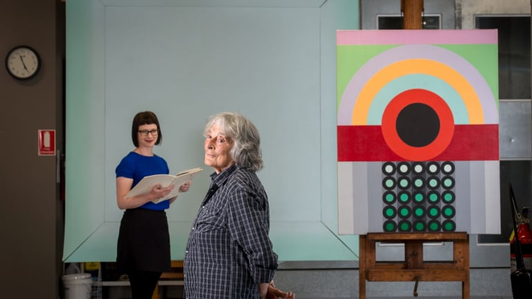 Artist Janet Dawson (front)  and NGV curator Beckett Rozentals, with John Peart's Corner square diagonal (rear) and James Doolin's Artificial landscape 67-6.