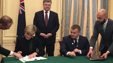 Foreign Minister Julie Bishop signed the agreement with Ukrainian Energy and Coal Industry Minister Volodymyr Demchyshyn (second from right) watched by Ukrainian President Petro Poroshenko (centre).