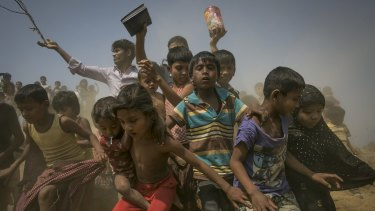 Rohingya refugees run to the crew of the Nautical Aliya as they provide relief supplies at the Balu Khali camp in Chittagong, Bangladesh, on Wednesday.