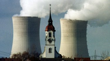 The church spire of the northern Bavarian village of Heidenfeld is dwarfed by the cooling towers of the Grafenrheinfeld nuclear power station.