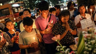 People pray for the victims of a bomb blast at the re-opened Erawan shrine in Bangkok.