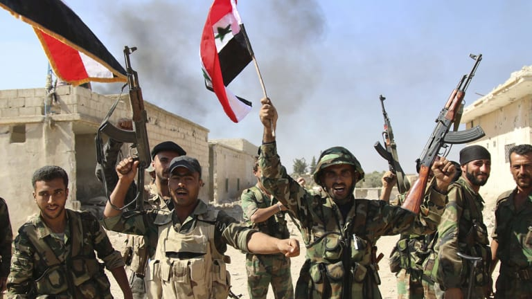 Syrian soldiers wave Syrian flags while celebrating the capture of Achan, Hama province, Syria, on Sunday.