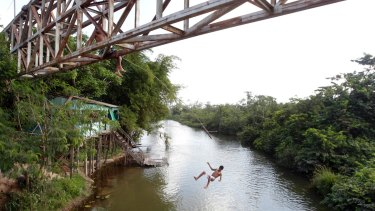 A young man jumps from an overpass into a river in Paragominas, northern state of Para near the reserve the Brazilian government wants to abolish to make way for mining.