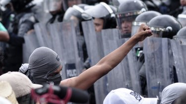 Protestors, some armed with machetes, were confronted by federal police in Acapulco.