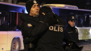Police officers comfort each other after explosions near the Besiktas football club stadium.