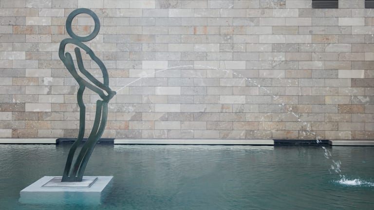 Julian Opie's Peeing boy fountain  in the moat at NGV International.