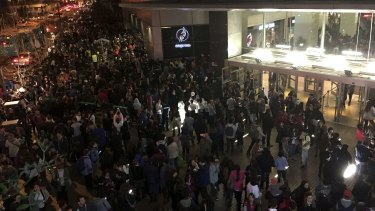 People evacuate a shopping mall in Santiago after a powerful earthquake hit off Chile's northern coast.