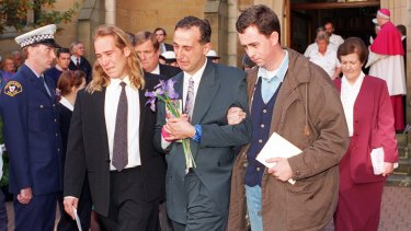 Walter Mikac is comforted by family and friends at the memorial service in May 1996 for the victims of the shooting in Tasmania.