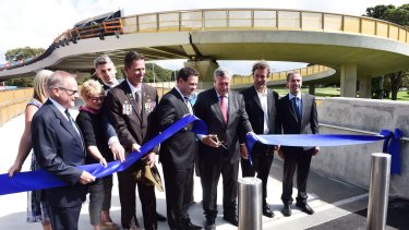 """Dignitaries including Duncan Gay (with scissors) open the Albert """"Tibby"""" Cotter walkway over ANZAC Parade earlier this year."""