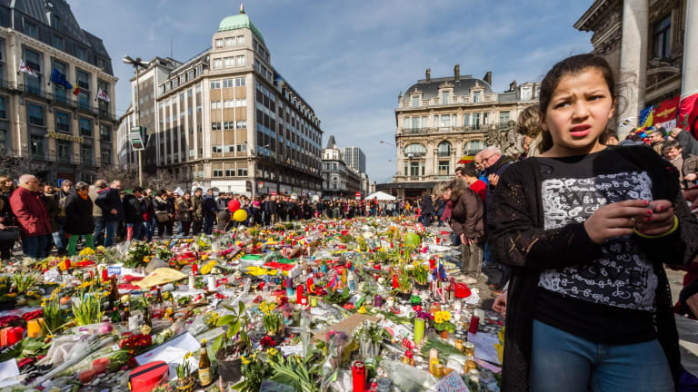People stop and look at floral tributes at a memorial site at the Place de la Bourse in Brussels, days after the attack.