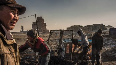 Workers sort coal at the Nalaikh mines on the outskirts of Ulaanbaatar. The air is cleaner in Nalaikh, despite the area being the primary source of the coal burned in the capital.