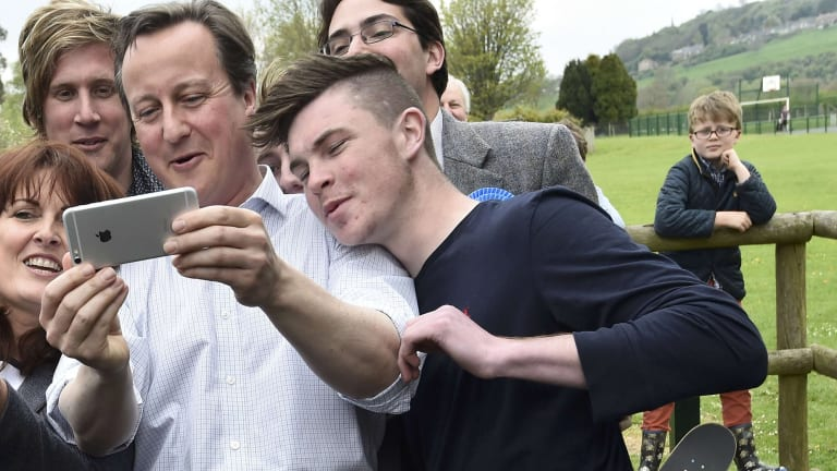 British Prime Minister David Cameron joins supporters for a selfie.