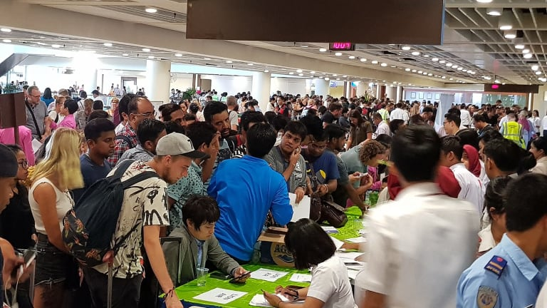 Crowds of passengers cram customer service desks set up at Denpasar airport's international terminal on Monday.