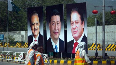 Workers walk past a billboard showing pictures of Chinese President Xi Jinping, centre, with Pakistani President Mamnoon Hussain, left, and Prime Minister Nawaz Sharif in Islamabad, Pakistan.